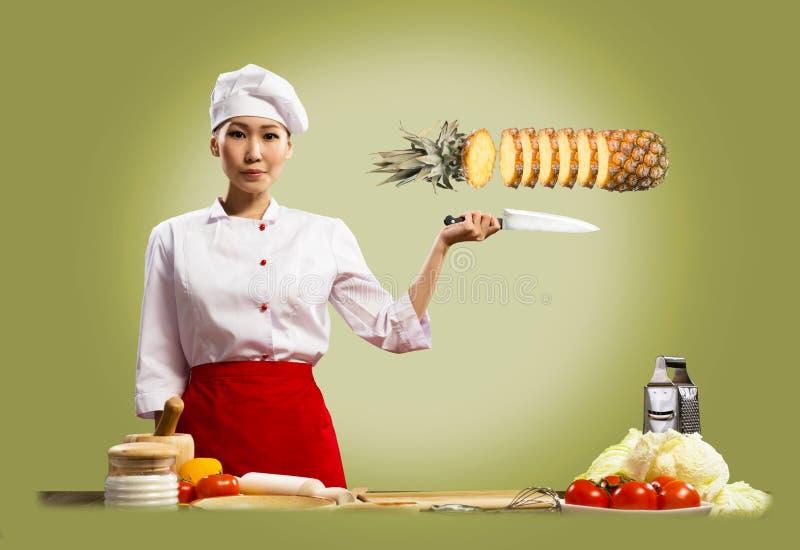 亚裔女性厨师切菠萝 库存照片