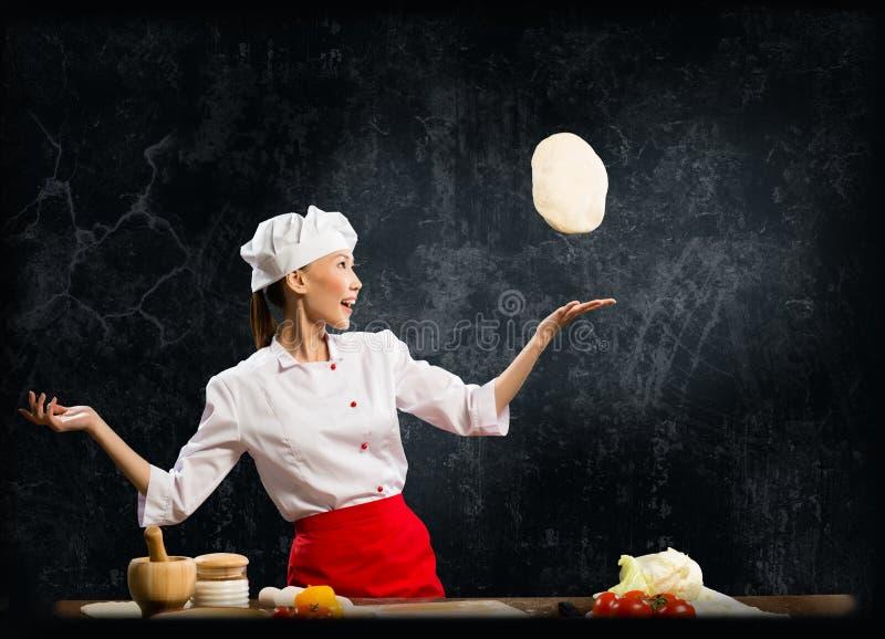 亚裔女性厨师扔面团片断  库存图片