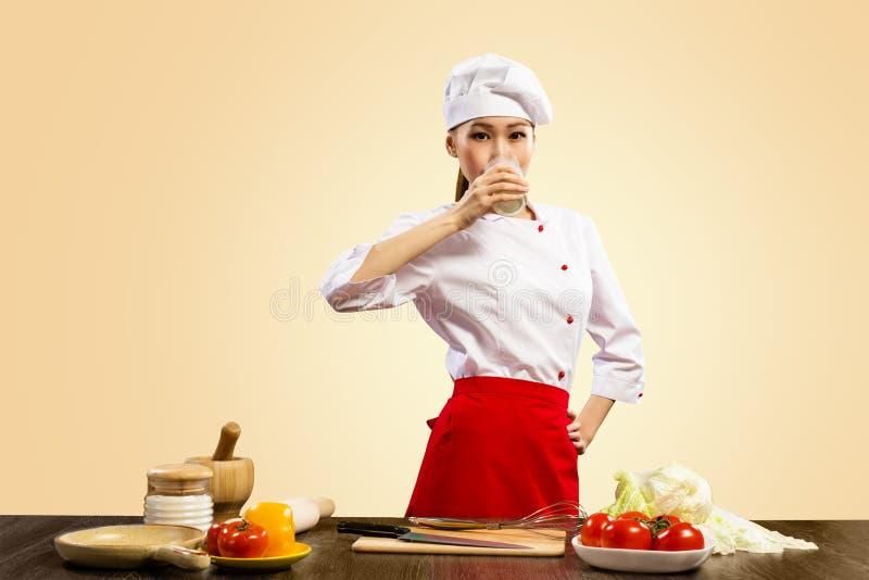 亚裔女性厨师饮用奶 免版税图库摄影
