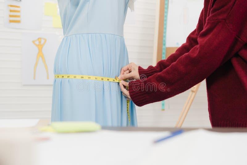 亚裔女性在一个时装模特衣物设计的时尚编辑运转的测量的礼服在演播室 免版税库存照片