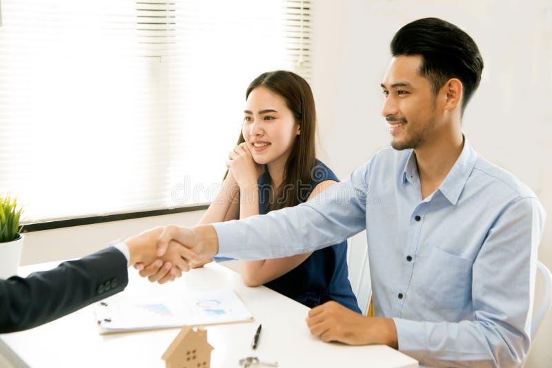 亚裔女性推销员在一次现代办公室屋子和谈话坐给顾客和满意对成功 免版税库存图片