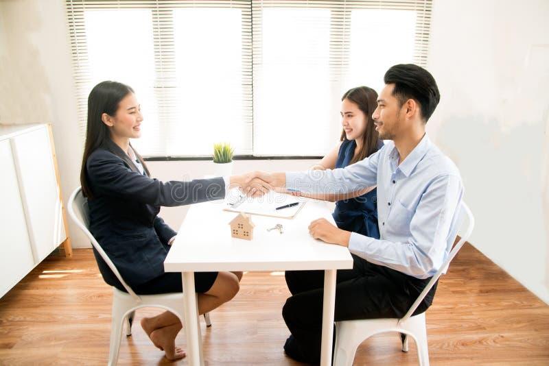 亚裔女性推销员在一次现代办公室屋子和谈话坐给顾客和满意对成功 库存照片