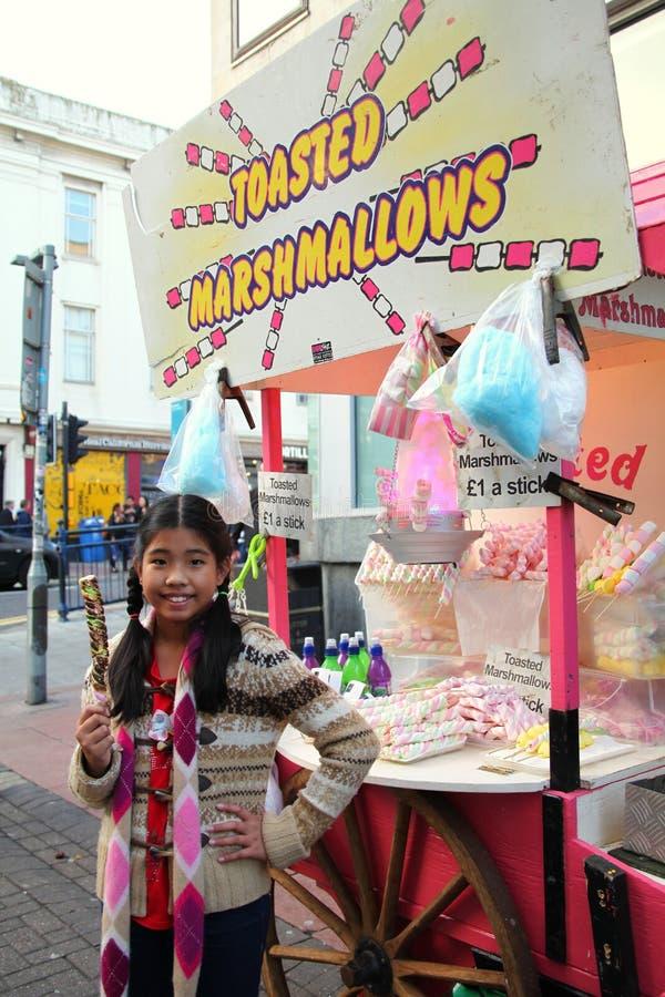 亚裔女性游人享用传统敬酒的蛋白软糖 免版税库存照片