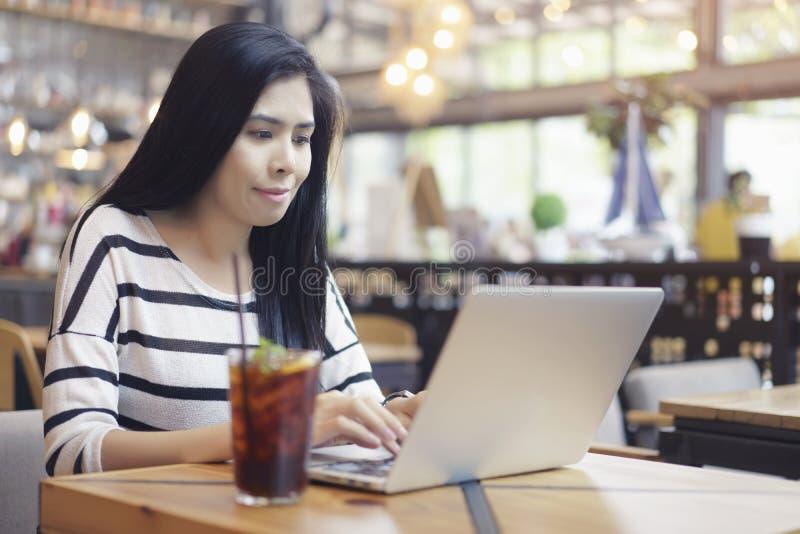 亚裔妇女与计划的议程和日程表一起使用在笔记本,使用计算机膝上型计算机工作新的项目,单独坐在咖啡馆 免版税库存图片
