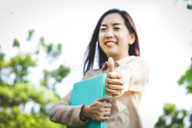 亚裔妇女举他们的手指 库存图片