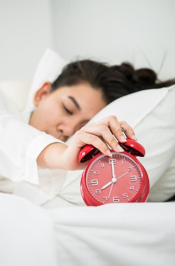 亚裔妇女从睡眠醒 她时钟的手举行和 库存照片