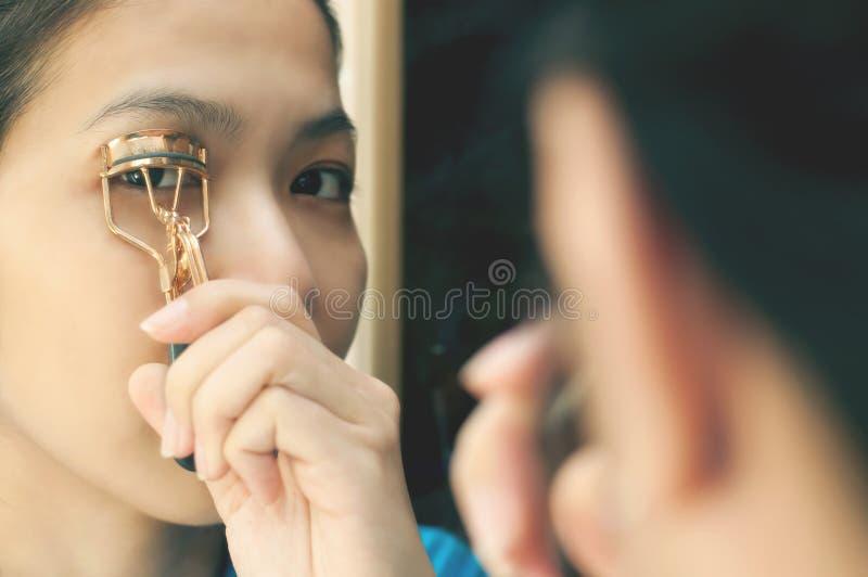 亚裔妇女使用睫毛卷发的人 图库摄影
