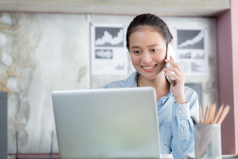 亚裔妇女使用膝上型计算机并且在办公室打电话 免版税库存图片