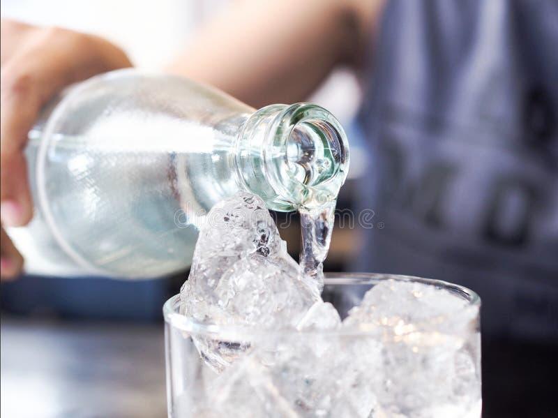 亚裔妇女倾吐在冰玻璃的干净的饮用水 免版税图库摄影