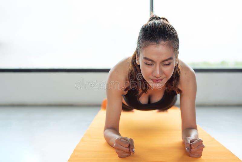 亚裔妇女健身女孩做板条在瑜伽席子的健身健身房 他 图库摄影