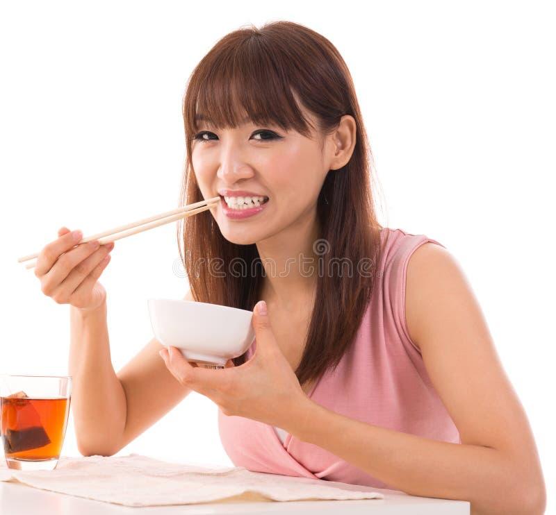亚裔妇女吃米 库存图片