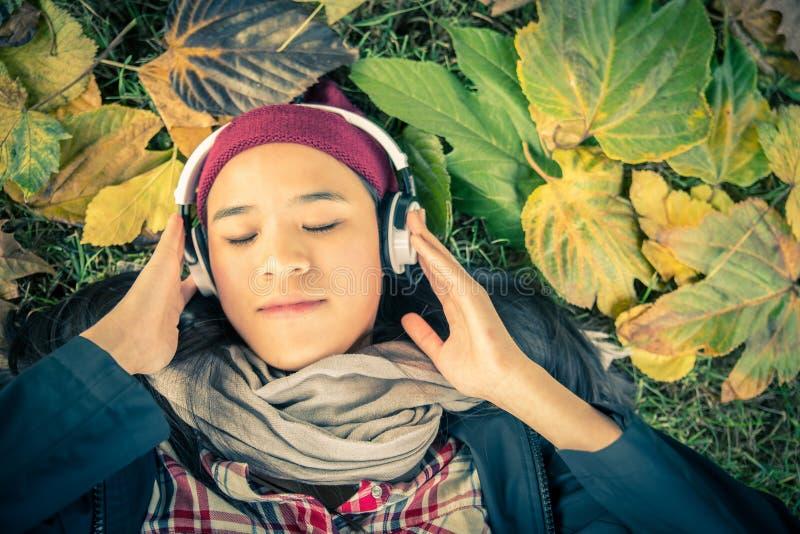 年轻亚裔妇女听的音乐在公园 免版税库存图片