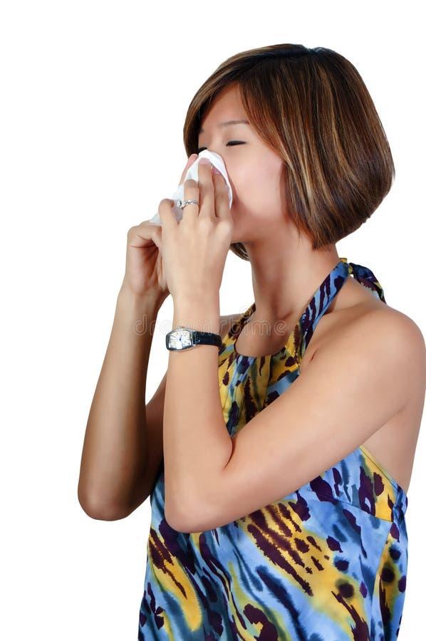 亚裔妇女吹的鼻子 库存照片