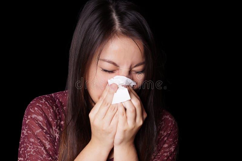 年轻亚裔妇女吹的鼻子 库存照片
