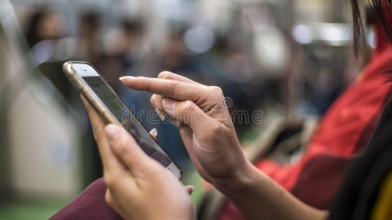 亚裔妇女在地铁和举行智能手机坐下 使用电话的乘客 免版税库存照片