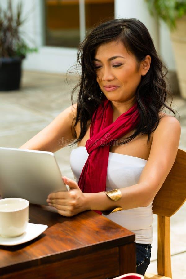 亚裔妇女在室外的酒吧或的咖啡馆坐 免版税库存图片