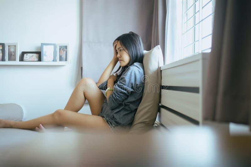 亚裔妇女在家坐卧室,女性感觉的头疼和迷茫的问题在生活,避孕和意想不到 库存图片