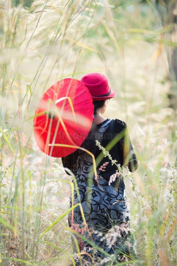 亚裔妇女在有红色的庭院里 库存照片