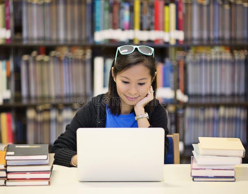 亚裔妇女在有膝上型计算机的图书馆里 库存照片