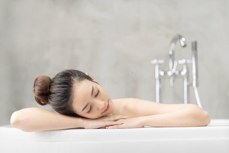 亚裔妇女在浴放松 免版税图库摄影