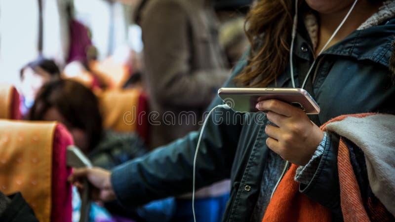 亚裔妇女在火车站起来 使用在地铁的智能手机 免版税图库摄影
