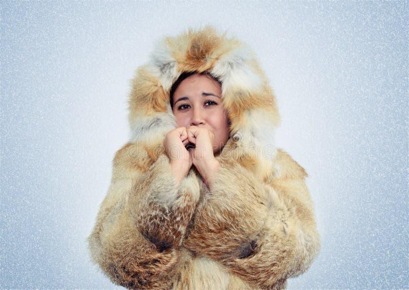 亚裔妇女在狐狸皮大衣温暖的手上,寒冷,雪,飞雪 免版税库存照片