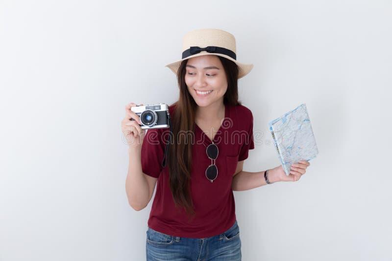 亚裔妇女在白色背景使用一台影片照相机射击 免版税图库摄影