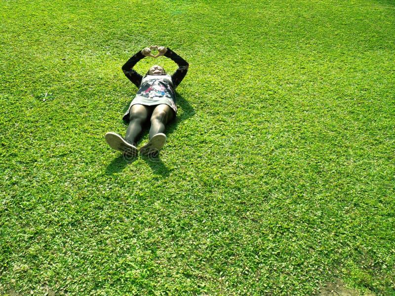 亚裔妇女在绿色草原放置 少女穿花和黑礼服 俏丽女性浪漫做心脏 库存照片