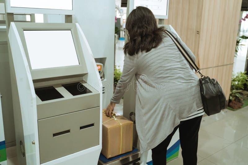 亚裔妇女在行李等级上把纸板放 免版税库存照片