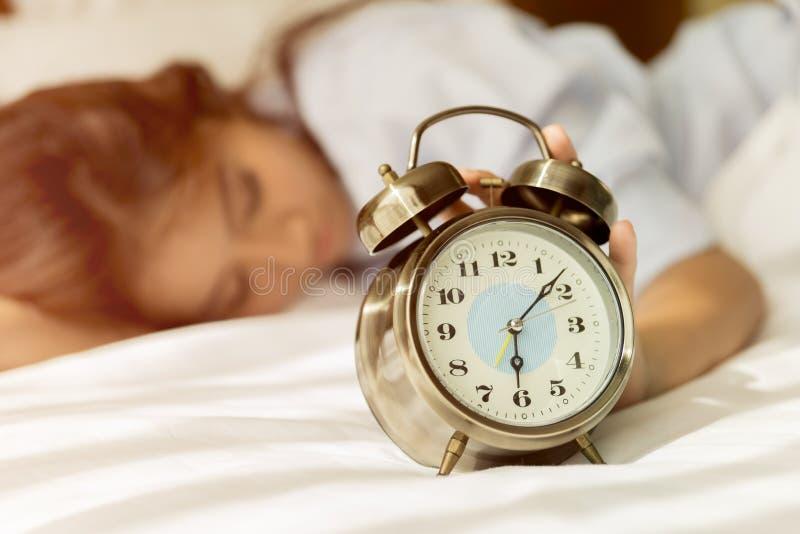 年轻亚裔妇女在设法的床上醒与闹钟 免版税图库摄影