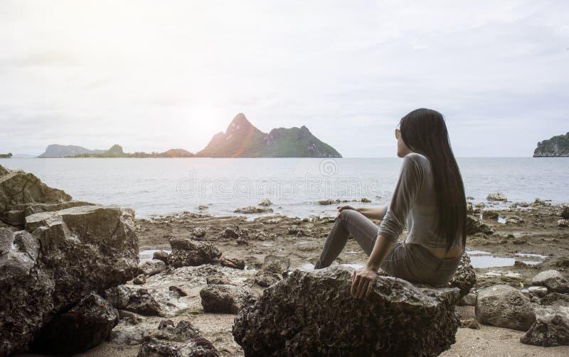 年轻亚裔妇女坐岩石在海附近,看对海、冷颤出于夏天,休息时间、光和增加的火光作用 库存图片