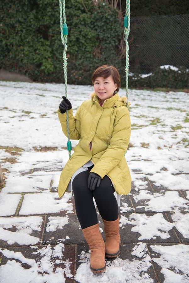 亚裔妇女坐摇摆在冬天,瑞士,欧洲 免版税库存照片