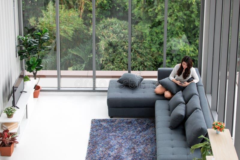 亚裔妇女坐有笔记本和耳机的沙发在大附近 图库摄影