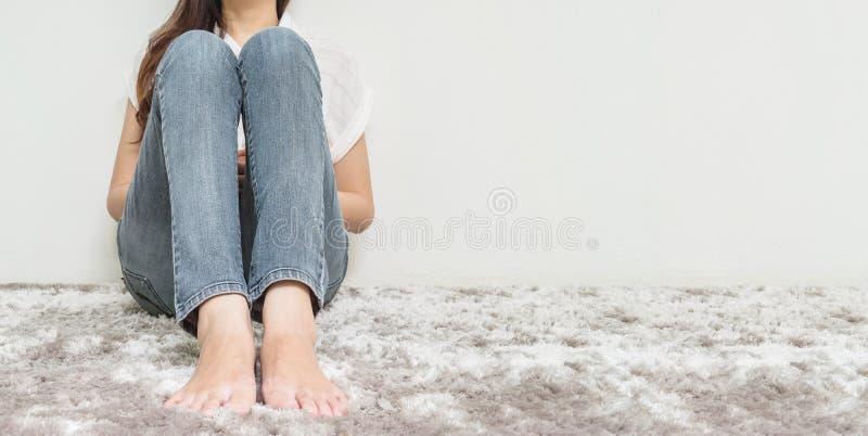 亚裔妇女坐灰色地毯地板有白水泥被构造的背景在房子的角落有拷贝空间的 免版税库存照片