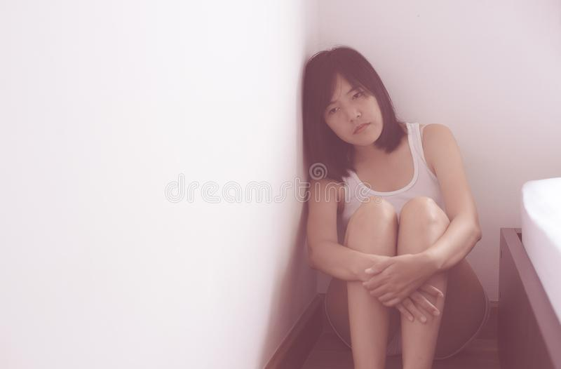 亚裔妇女坐,并且拥抱他的由胸口消沉决定的膝盖有头疼在她的卧室 库存图片