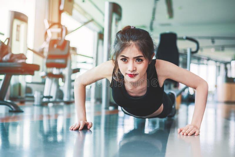 亚裔妇女女孩做推挤的健身上升在健身健身房 医疗保健和健康概念 训练和身体组合题材 ?? 库存图片