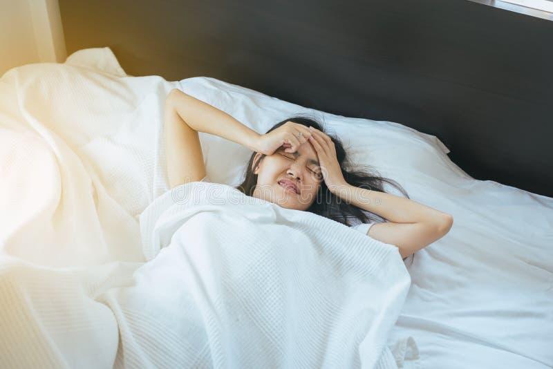 亚裔妇女安排在床上的头疼以后醒早晨 免版税库存照片