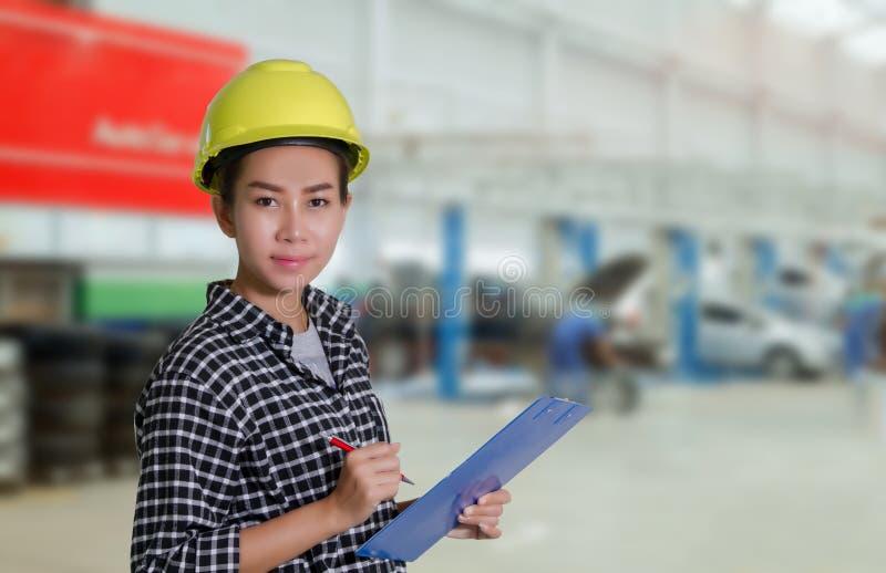 亚裔妇女工程师和技术员技工检查和在一辆汽车的板的inspectingthe名单在汽车修理店的 图库摄影