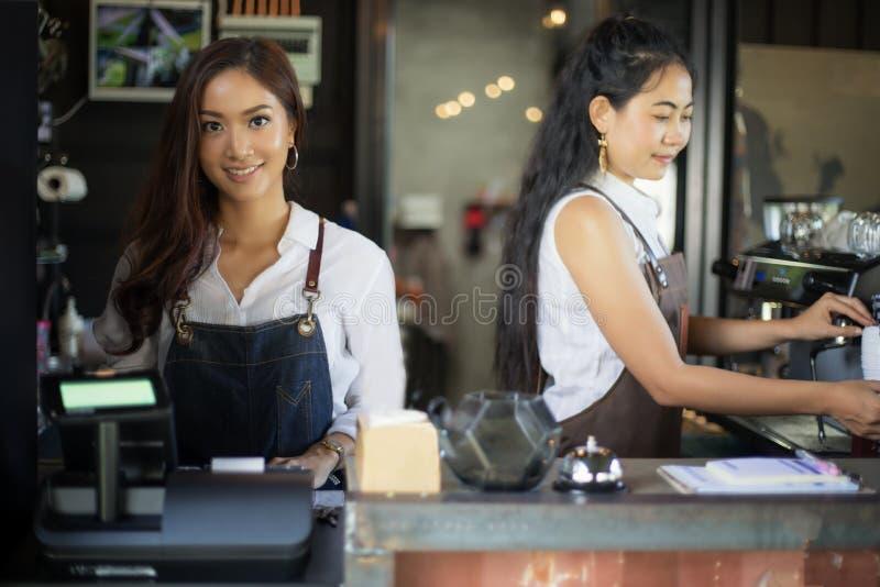 亚裔妇女微笑和使用咖啡机器的Barista在咖啡s 免版税库存图片