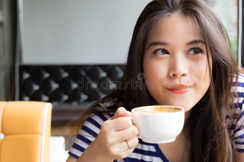 亚裔妇女微笑的和饮用的咖啡 库存图片