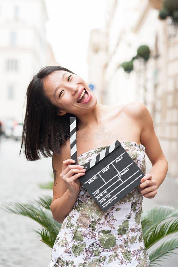 年轻亚裔妇女微笑的展示拍板 库存照片