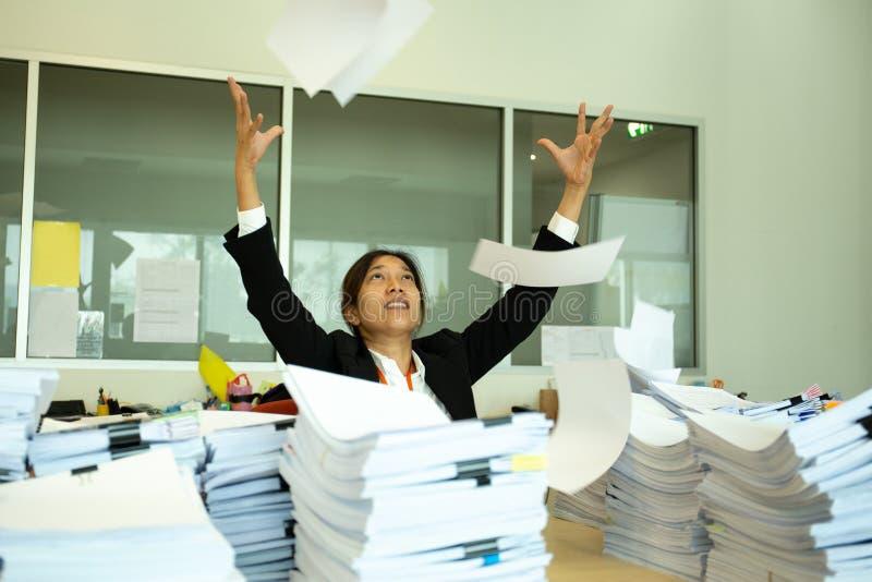 亚裔妇女投掷的纸张文件,当研究项目在办公室时 免版税库存照片