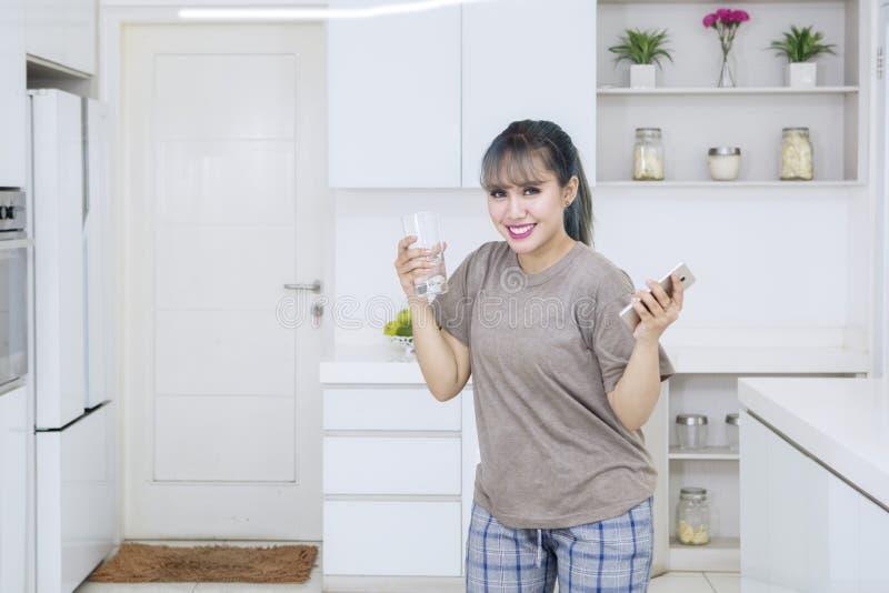 亚裔妇女拿着电话和杯水 库存照片