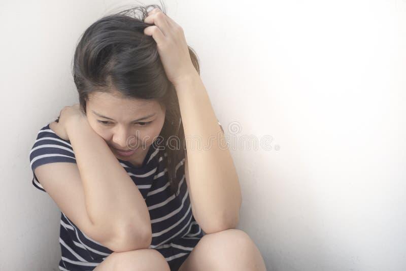 亚裔妇女是失望坐地板和看下来在腿之间有白色背景 免版税图库摄影