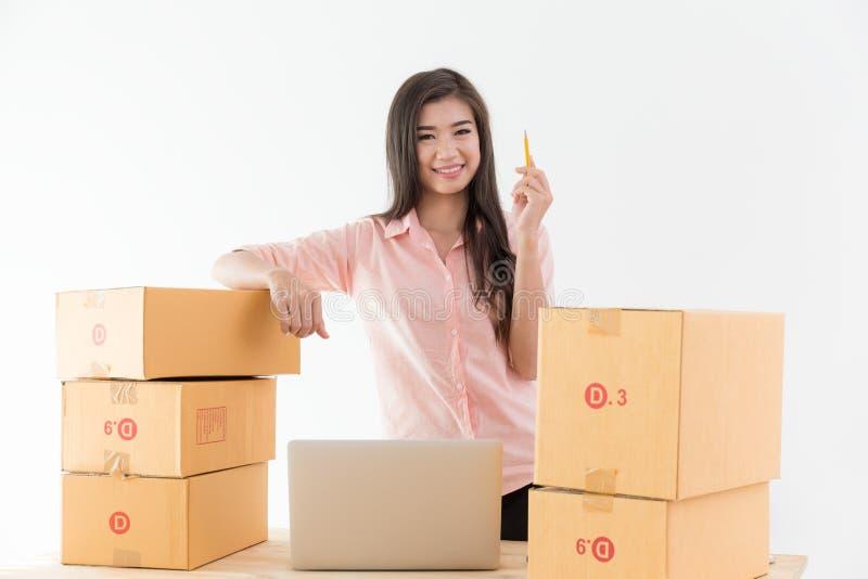 亚裔妇女是微笑和记录顾客定货,事务o 库存照片