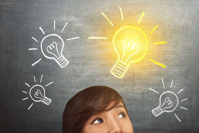 年轻亚裔妇女有与明亮的电灯泡天花板的想法 免版税库存照片