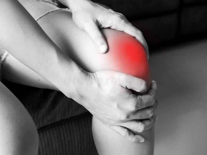 亚裔妇女有深刻膝盖受伤和遭受腿抽筋 免版税库存图片