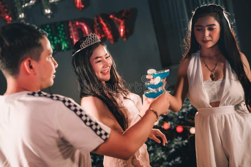 亚裔妇女生日宴会朋友与生日蛋糕和饮用的鸡尾酒的大惊奇燃烧蜡烛 图库摄影