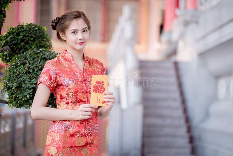 亚裔妇女用中文穿戴拿着对联'愉快' (脊椎 图库摄影