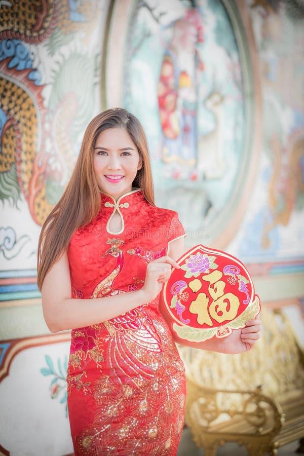 亚裔妇女用中文穿戴拿着对联'愉快' (脊椎 免版税库存照片
